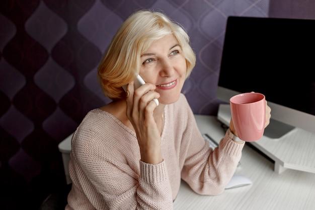 Mulher madura sorridente usando telefone celular enquanto trabalha pelo computador em casa