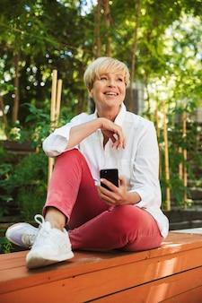 Mulher madura sorridente usando telefone celular