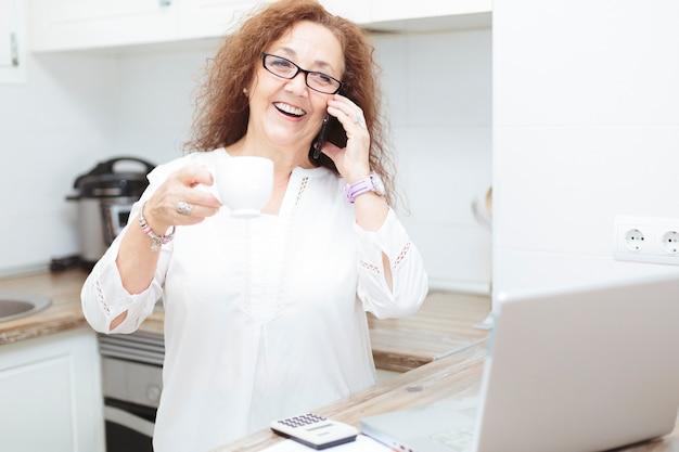 Mulher madura, sorrindo ao telefone, segurando uma xícara de café.