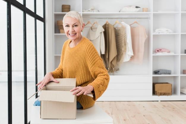 Mulher madura, sorrindo e posando com caixa