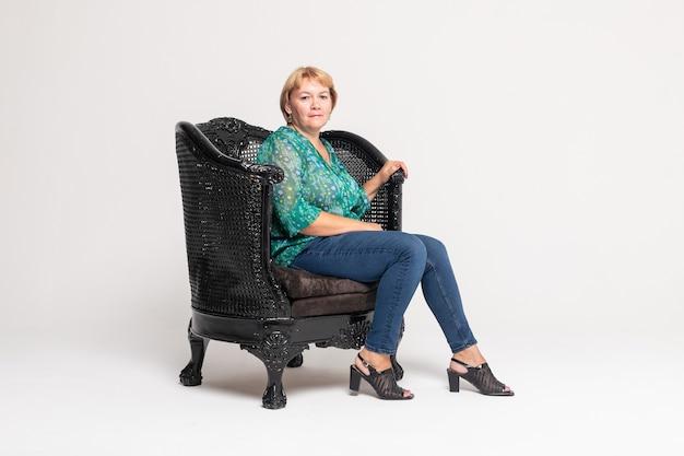 Mulher madura sorrindo e sentada em uma poltrona isolada no fundo branco