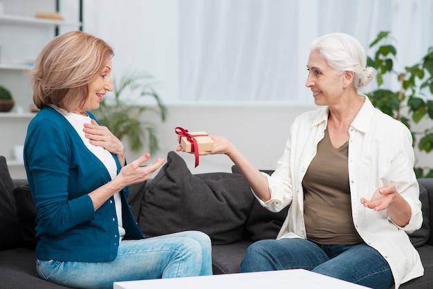 Mulher madura, surpreendendo sua amiga com um presente