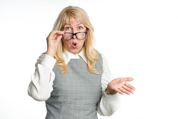 Mulher madura surpresa em copos gesticula suas emoções sobre um fundo claro.