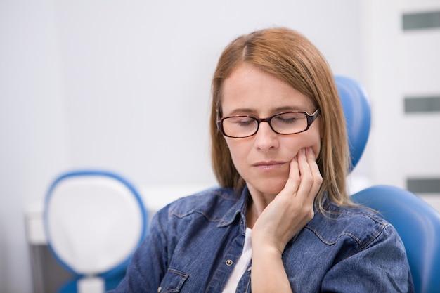 Mulher madura tendo dor de dente, tendo uma consulta odontológica
