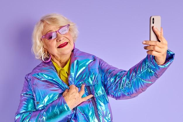 Mulher madura tirando foto, selfie no smartphone, usando roupas quentes elegantes