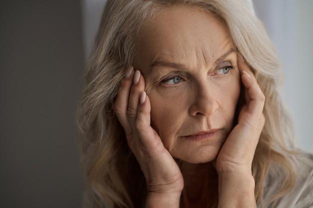 Mulher madura triste com dor de cabeça