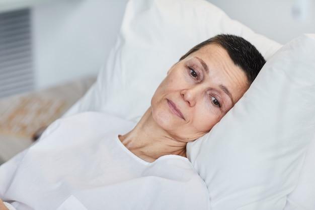 Mulher madura triste deitada na cama e se recuperando no hospital