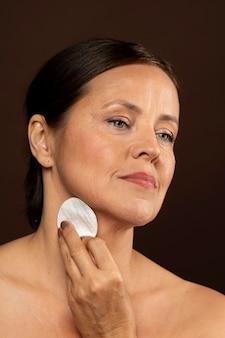 Mulher madura usando almofada de algodão para remover maquiagem
