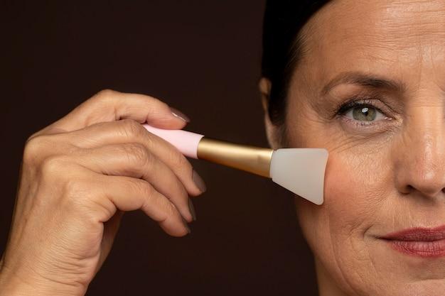 Mulher madura usando escova facial de quartzo rosa