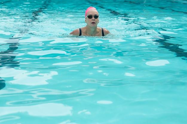 Mulher madura usando óculos de proteção enquanto nada na piscina