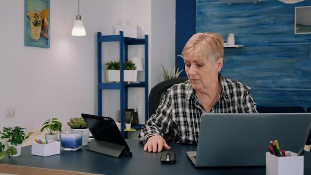Mulher madura usando tablet e laptop ao mesmo tempo, analisando gráficos financeiros trabalhando em casa, sentada no local de trabalho