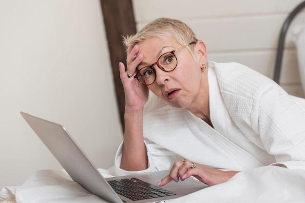 Mulher madura, usando um laptop na cama
