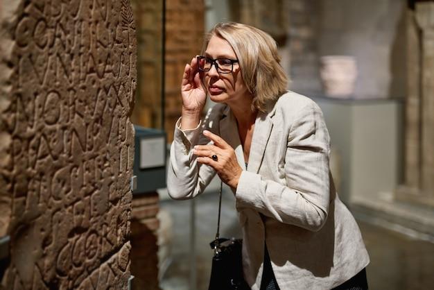 Mulher madura visitando museu de antiguidades