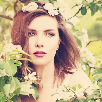 Mulher magnífica com garota de fundo de flor de primavera ao ar livre