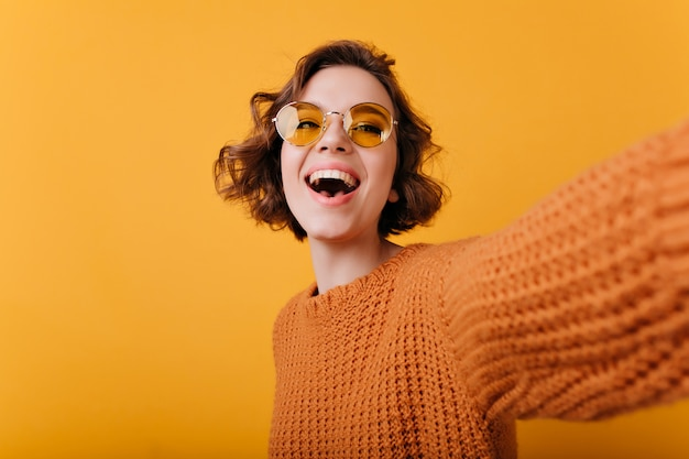 Mulher magnífica rindo em óculos de sol amarelos engraçados, fazendo selfie. retrato de menina branca relaxada na camisola de malha, tirando foto de si mesma.