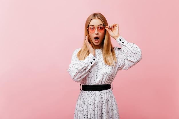 Mulher magnífica surpresa em um vestido longo, de pé na rosa. adorável modelo feminino em óculos de sol expressando espanto.