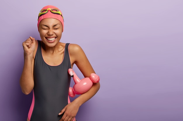 Mulher magra alegre usa maiô preto, chapéu de natação e óculos de proteção, fecha os punhos, comemora aprendendo a nadar, segura o flutuador de flamingo rosa de verão, isolado na parede roxa. conceito de esportes aquáticos
