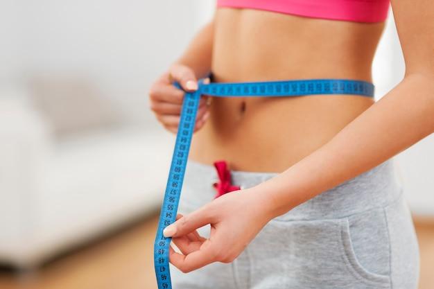 Mulher magra com fita métrica