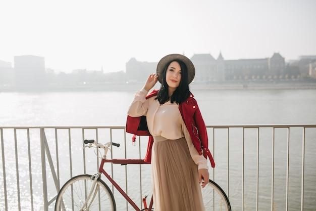 Mulher magra com jaqueta vermelha em pé com bicicleta no aterro