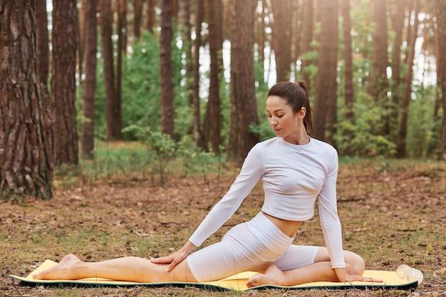 Mulher magra com rabo de cavalo em uma roupa esportiva da moda branca, sentada no tatame, praticando ioga, fazendo exercícios de alongamento