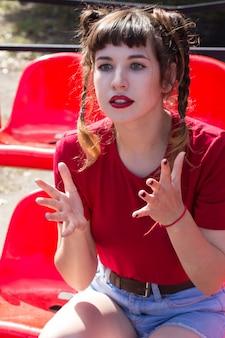 Mulher magra com tranças em uma camisa res e jeans short, sentada em um assento de plástico vermelho no estádio