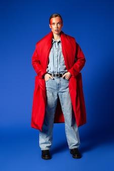 Mulher magra de corpo inteiro em roupas casuais, segurando as mãos nos bolsos e olhando para a câmera em pé contra um fundo azul