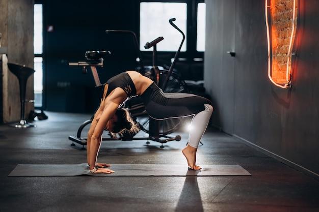 Mulher magra e atlética alongando as costas, fazendo exercícios de bridge na academia