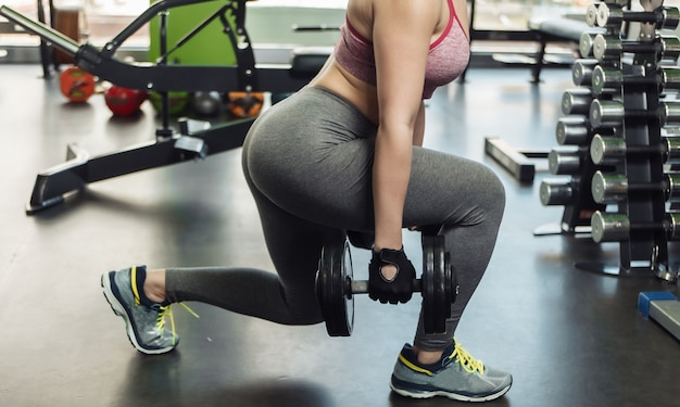 Mulher magra em roupas esportivas praticando estocadas com halteres na academia