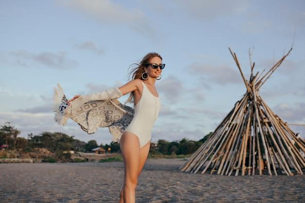 Mulher magra entusiasmada em óculos de sol, aproveitando a brisa do mar.