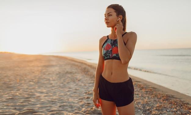 Mulher magra graciosa em pé na praia e relaxando após um treino intenso. mulher morena ouvindo música fazendo uma pausa após o exercício ao ar livre.