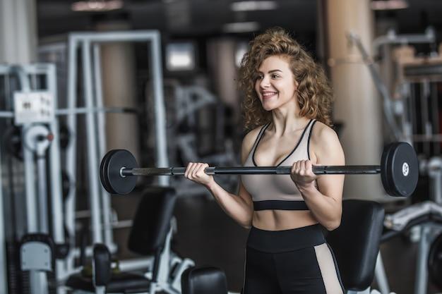Mulher magra, loira, vestindo roupas esportivas com halteres em uma academia, se exercitando com uma barra