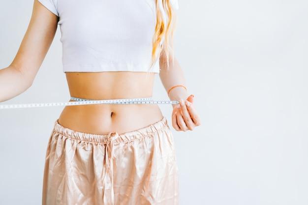 Mulher magra medindo o tamanho da cintura com fita métrica em fundo branco. perda de peso com sucesso.