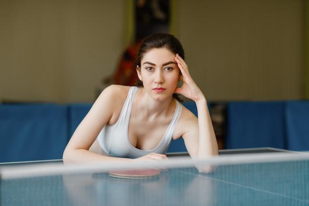 Mulher magra posa na mesa de pingue-pongue dentro de casa