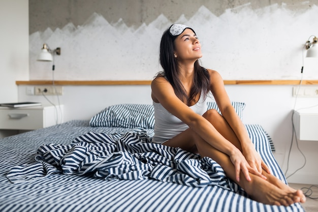 Mulher magra sorridente e atraente de pijama deitada na cama em casa descansando acorda de manhã