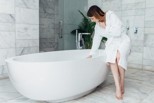 Mulher magra vestindo roupão de banho, sentada na borda da banheira se enchendo de água.