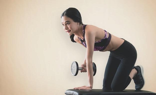 Mulher magro asiática forte está levantando halteres em fitness