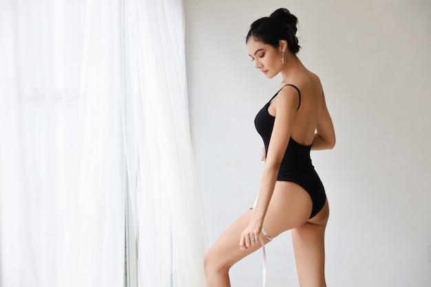 Mulher magro atraente e esportiva, medindo a cintura por fita métrica