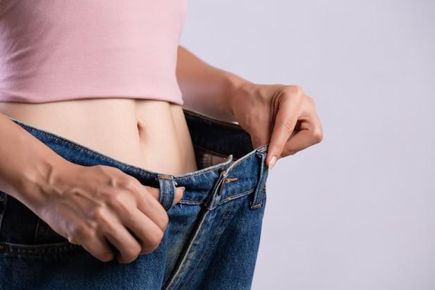 Mulher magro em calças de ganga de grandes dimensões.