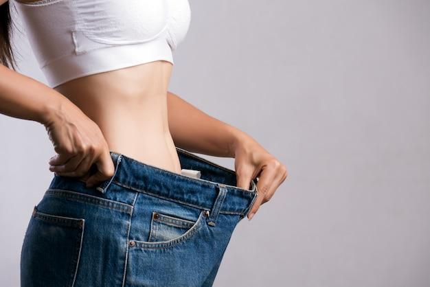 Mulher magro em jeans azul de grandes dimensões