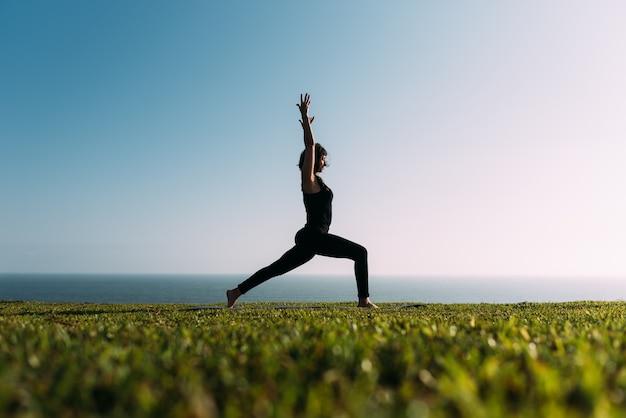 Mulher magro fazendo ioga na grama em frente ao mar ao ar livre