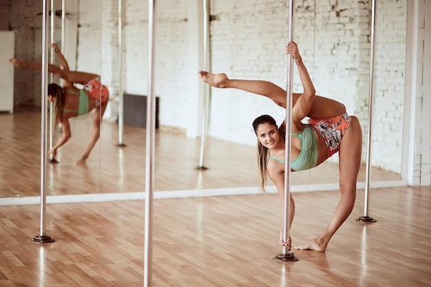 Mulher magro feliz realiza pole dance no estúdio