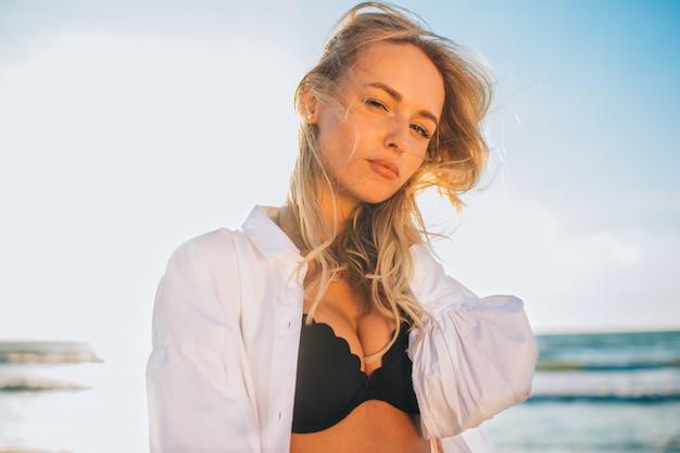 Mulher magro loira bonita em um biquíni preto e camisa branca na praia o oceano contra o sol.