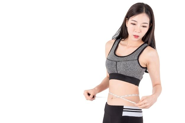 Mulher magro medindo a cintura dela usando uma fita métrica isolada no fundo branco