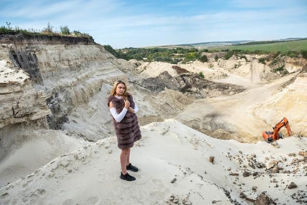 Mulher magro muito feliz com casaco de pele nas rochas de areia na natureza. estilo de vida