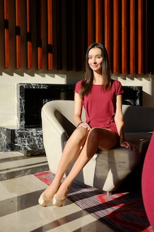 Mulher magro positiva com pernas longas em calças justas bege e estiletes no lobby