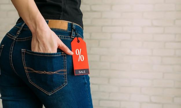 Mulher magro vista recortada em jeans com rótulo preto sexta-feira, copie o espaço.