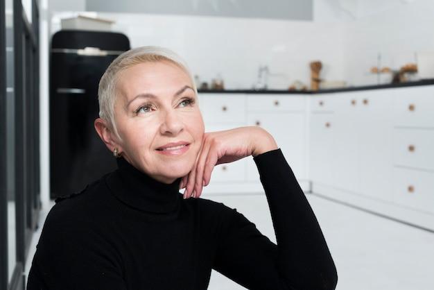Mulher mais idosa pensativa posando na cozinha