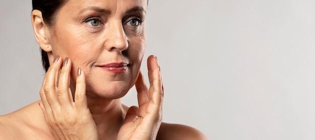 Mulher mais velha com maquiagem, posando com as mãos no rosto e copie o espaço