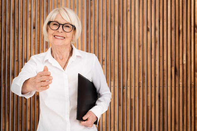 Mulher mais velha com uma prancheta no fundo de madeira