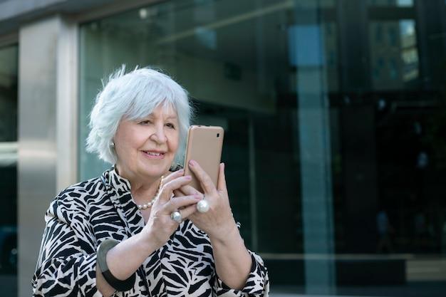 Mulher mais velha, de cabelos grisalhos, sorrindo com o celular na mão na rua